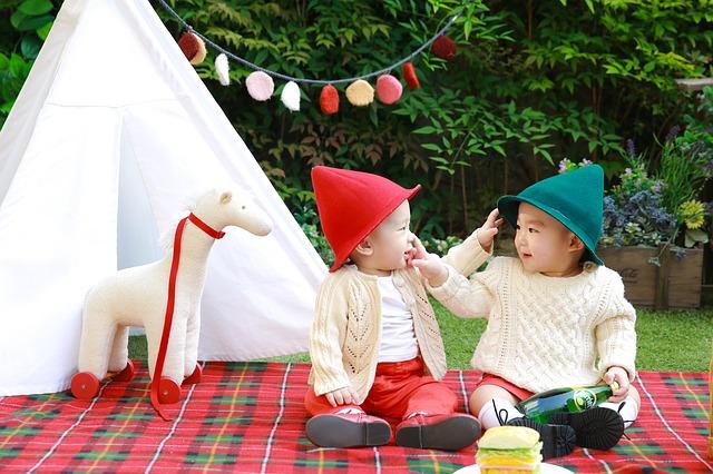 帽子を被った男の子2人がピクニックしている画像