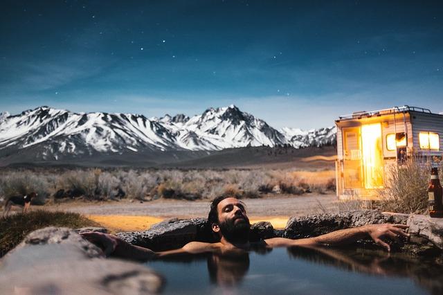 景色の良い露天風呂に入っている男性の画像