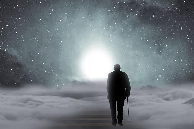 雲の上を歩いている杖をついた男性の後ろ姿のイメージ画像