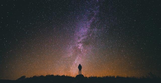 星空の下に立っている人のシルエットの画像