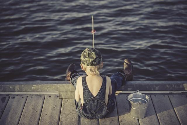 釣りをしている子供の後ろ姿の画像
