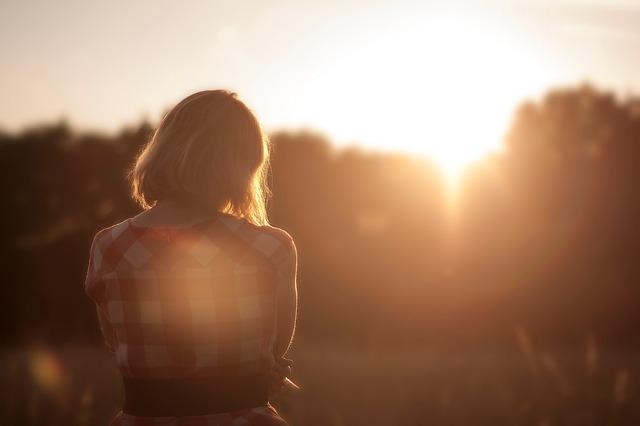 夕日に照らされる女性のシルエットの画像