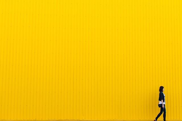 黄色の壁の前に歩いている女性の画像