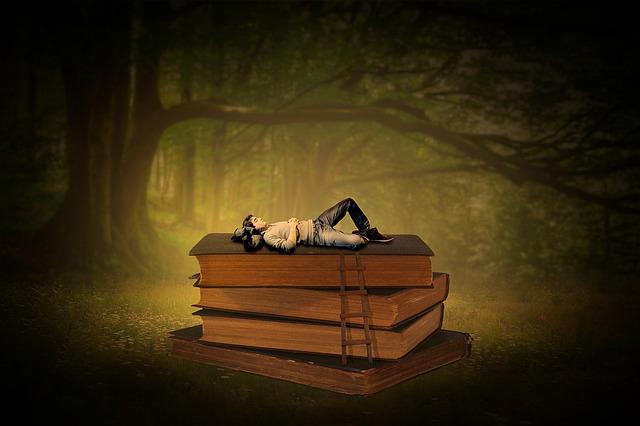 本の上で寝ている男性のイメージ画像