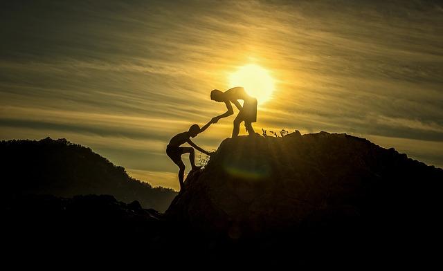 崖を登るのを手伝っている人の画像