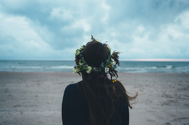 褒めるよりも褒められたい女性が海を見て悩んでいる画像