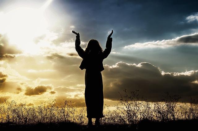 空に向かってパワーをもらっている女性の画像