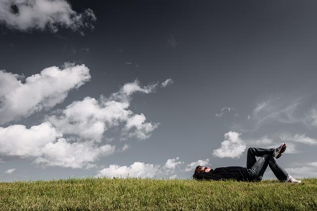 自分を見失い芝生で寝ている男性の画像