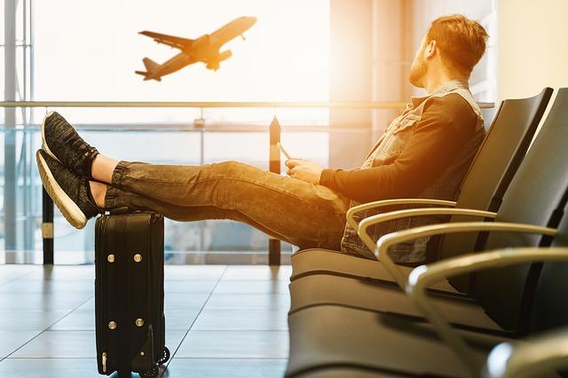 旅行に一緒に行く友達がいなくて一人で空港に来た男性の画像