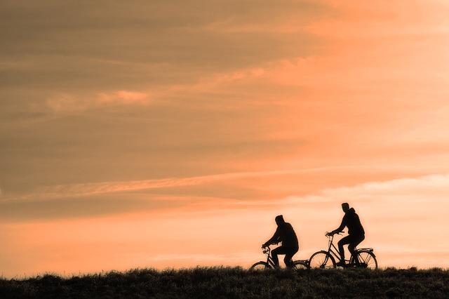 夕焼けの道を自転車を乗っている2人の画像