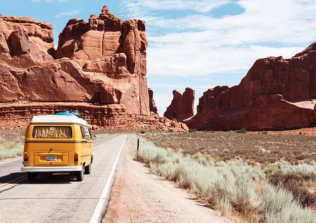 アメリカの道を走っている黄色い車の画像