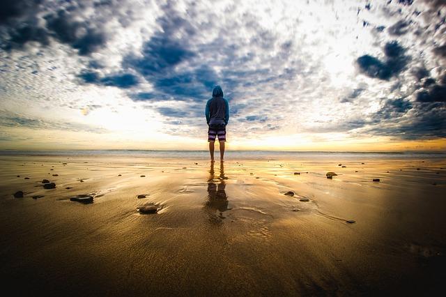 潮の引いた浜辺に立っている男性の後ろ姿の画像