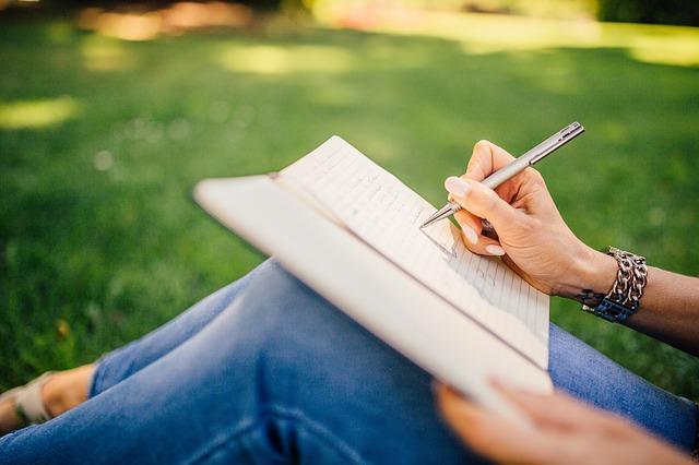 バケットリストをノートに書いている女性の画像