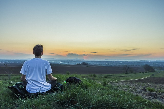 景色の良いところで瞑想している男性の画像