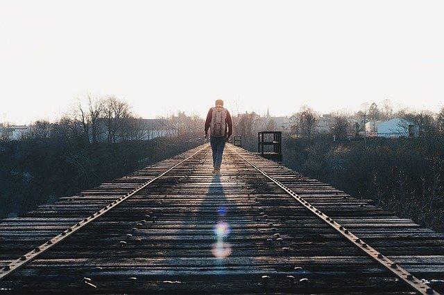 線路を渡る男性の後ろ姿の画像