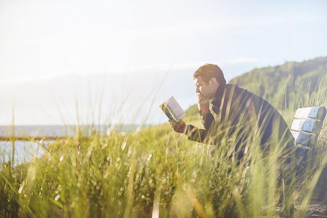 外のベンチで読書している男性の画像