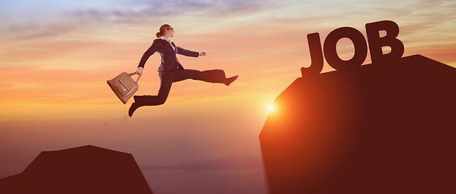 崖をジャンプしている会社員女性の画像