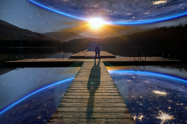 地球の下に立っている男性の後ろ姿の画像
