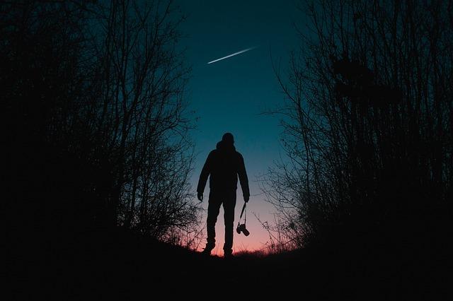 星空の下に立つ男性の画像