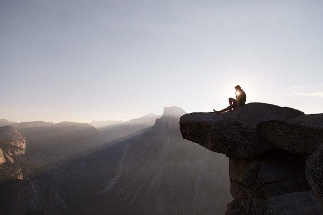 崖のはじっこで瞑想している男性の画像