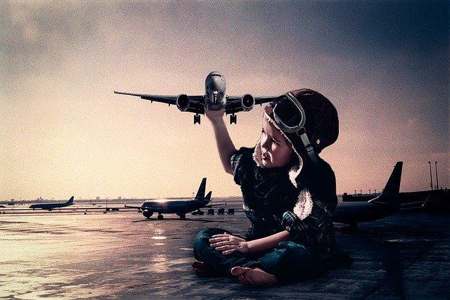 一人の子供が飛行機を持っているイメージ画像
