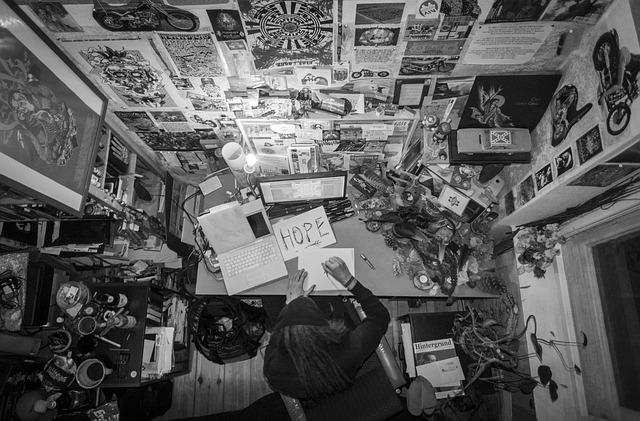 写真だらけの部屋で仕事している男性の画像