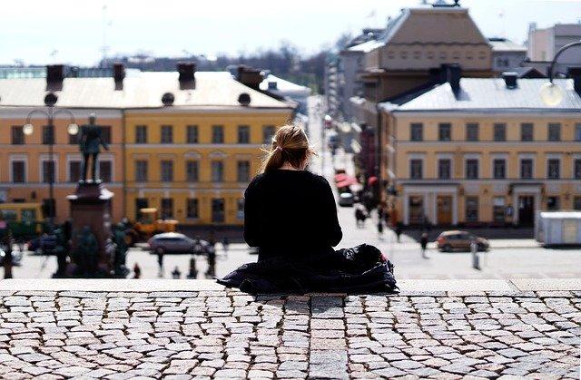 階段で読書している女性の後ろ姿の画像