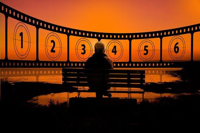 ひとり映画をしている男性の後ろ姿の画像