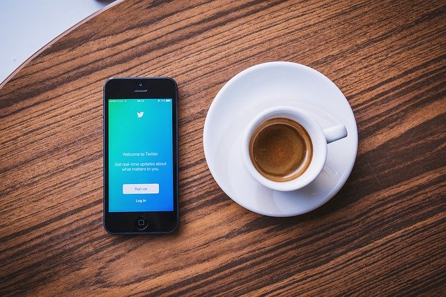 Twitterを開いたスマホとコーヒーの画像