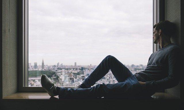 ひとりぼっちで外を眺める男性の画像