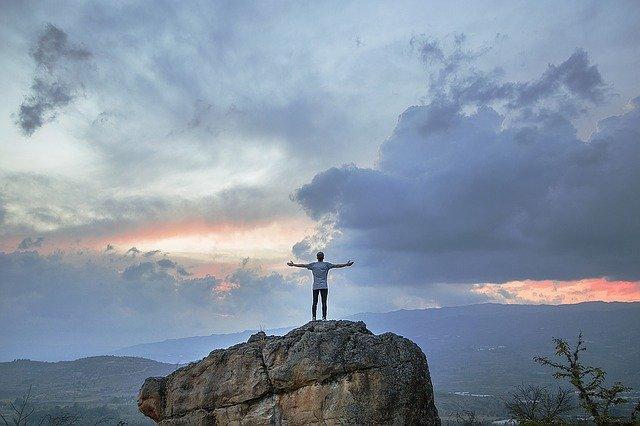 崖に大きく手を広げている男性の後ろ姿の画像