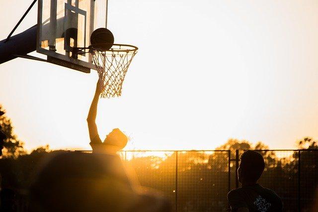 夕焼けの中でバスケをしている男性の画像