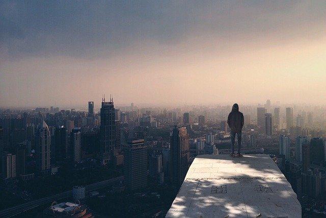 高いところに立ってため息をついている男性の後ろ姿の画像