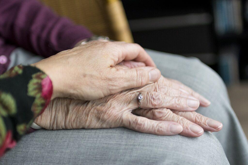 介護士が利用者さんの手を握っている画像