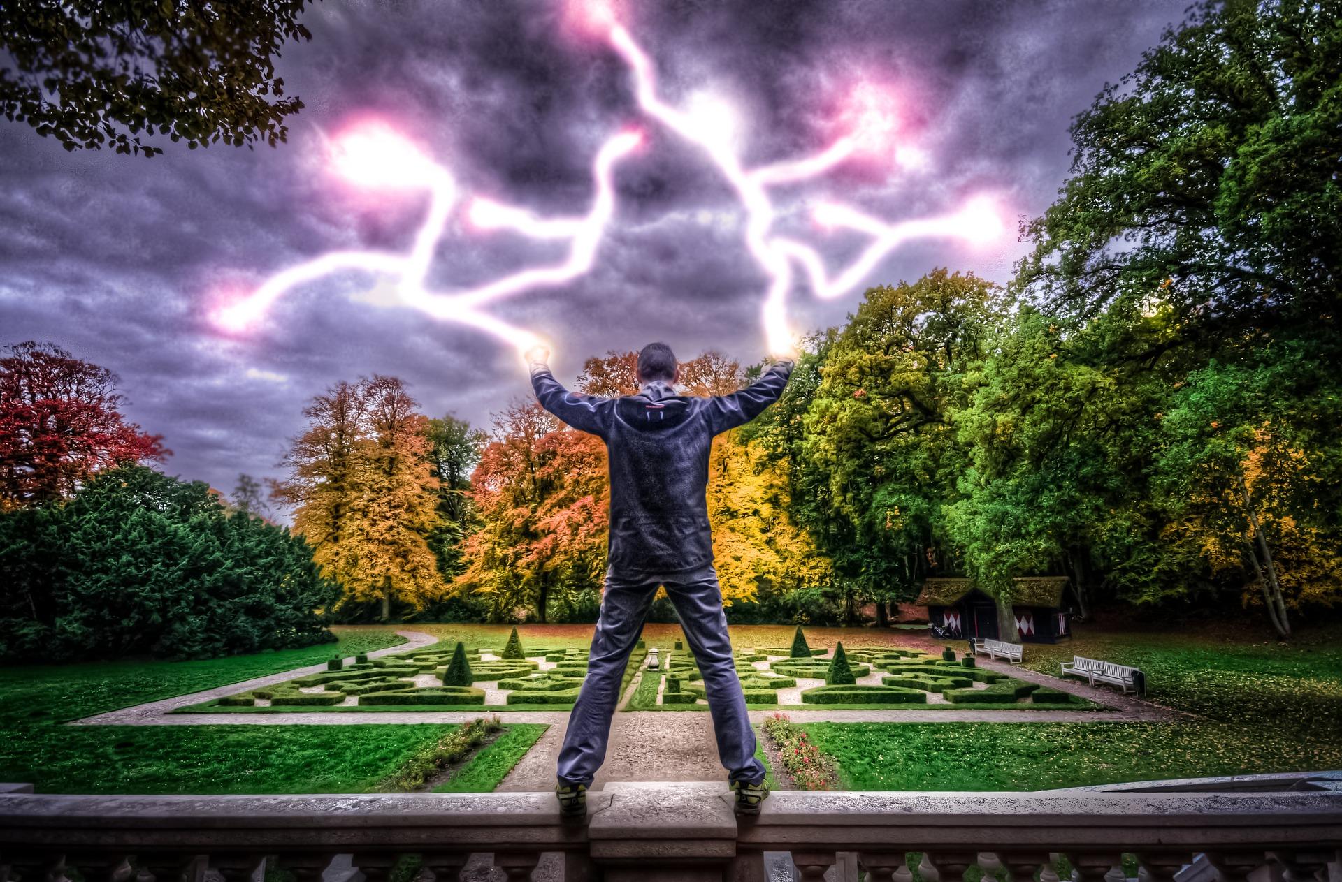 人生が終わるような手から電撃を放つ男性の後ろ姿の画像