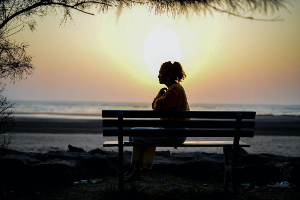 友達が少ないことに悩んでいる女性がベンチに座っている画像