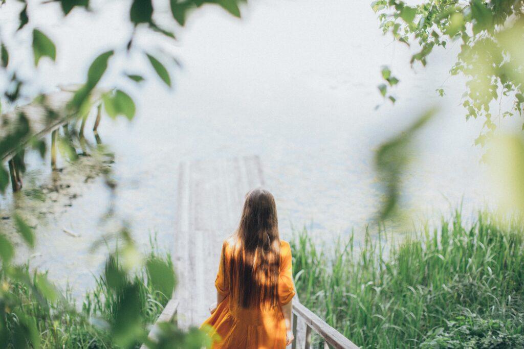 一人で池を眺めている女性の後ろ姿の画像