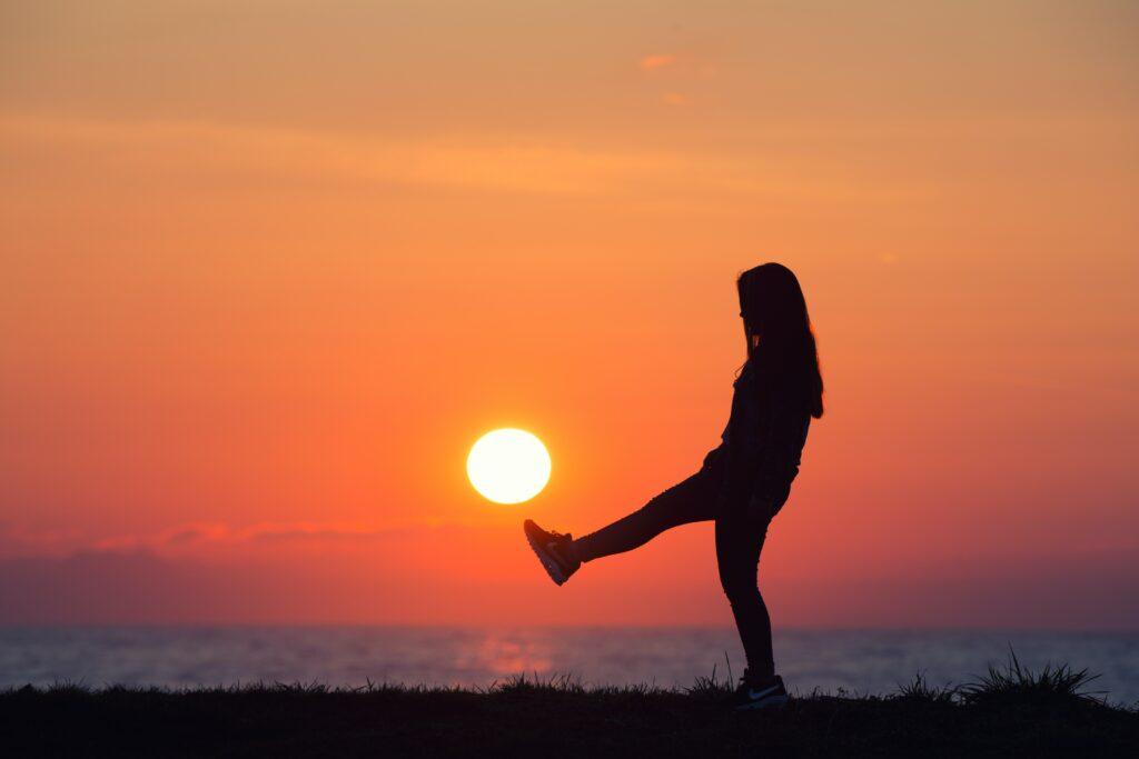 夕焼けをバックに映る一人の女性のシルエット画像