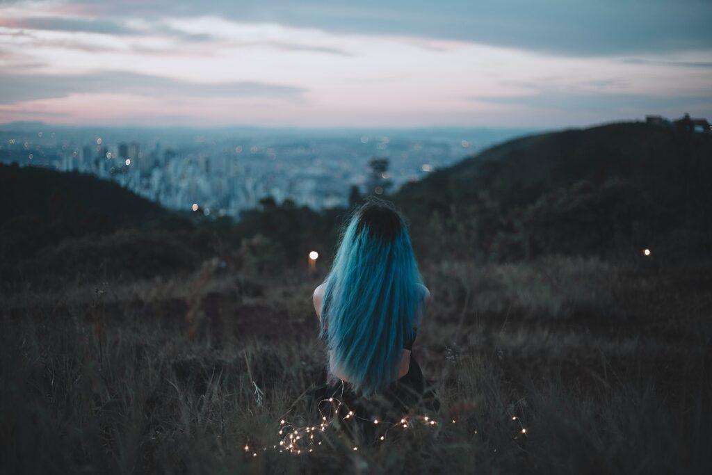 独りで景色を眺める青髪の女性の後ろ姿の画像