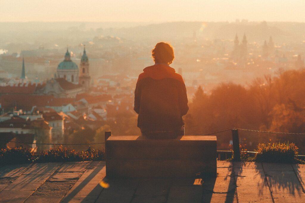 街の風景を見ている男性の後ろ姿の画像