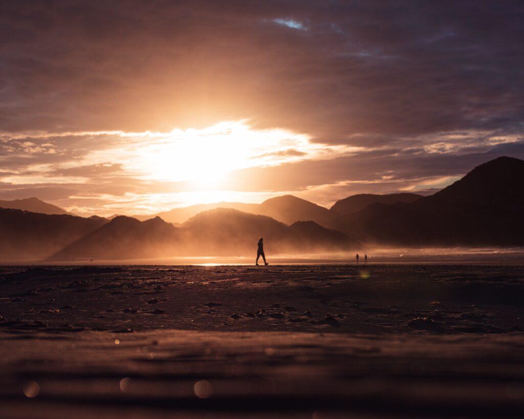 人生に光が差し込んだような夕日に照らされた海と人のシルエットの画像