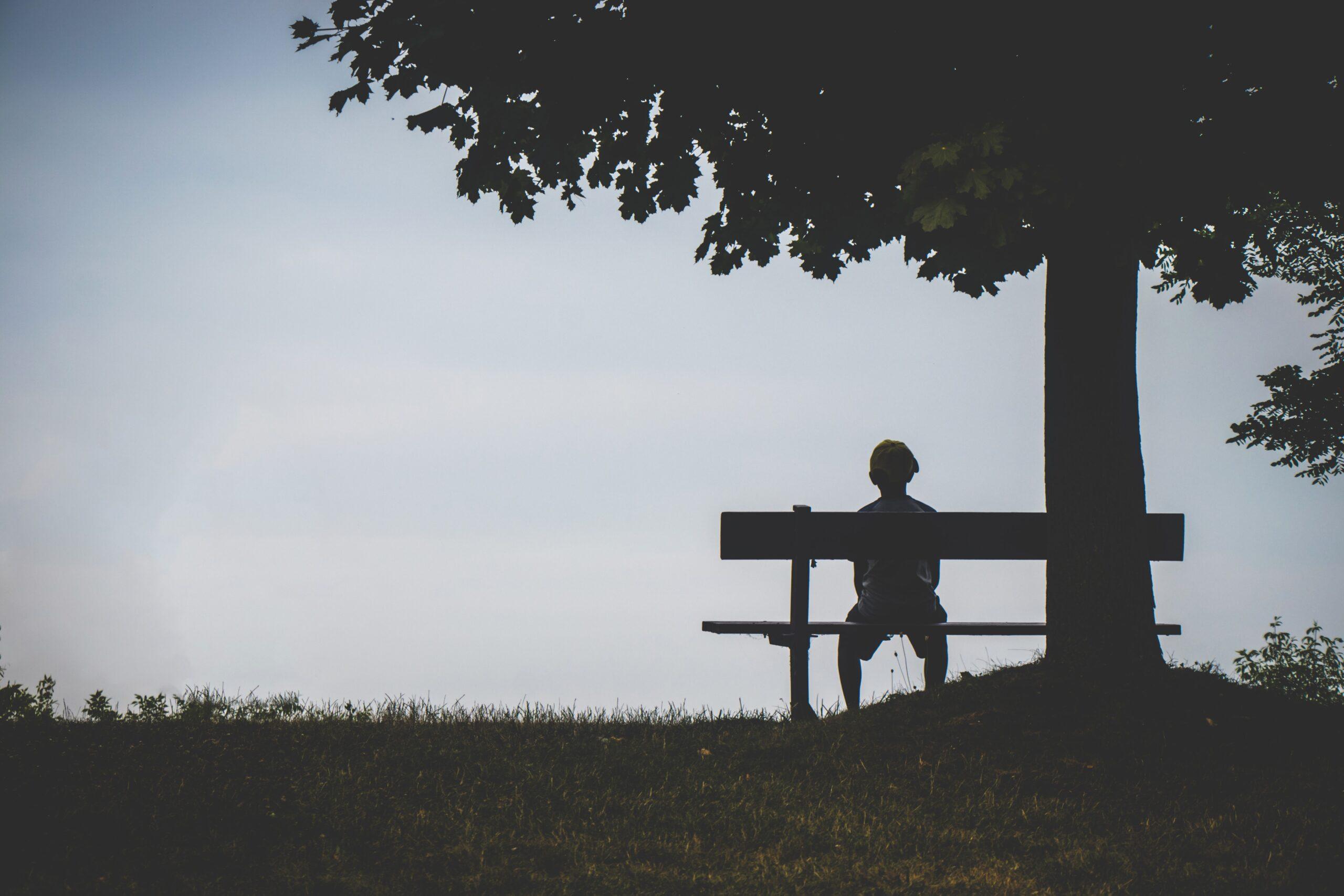 人生に絶望を感じている男性がベンチに座っている画像