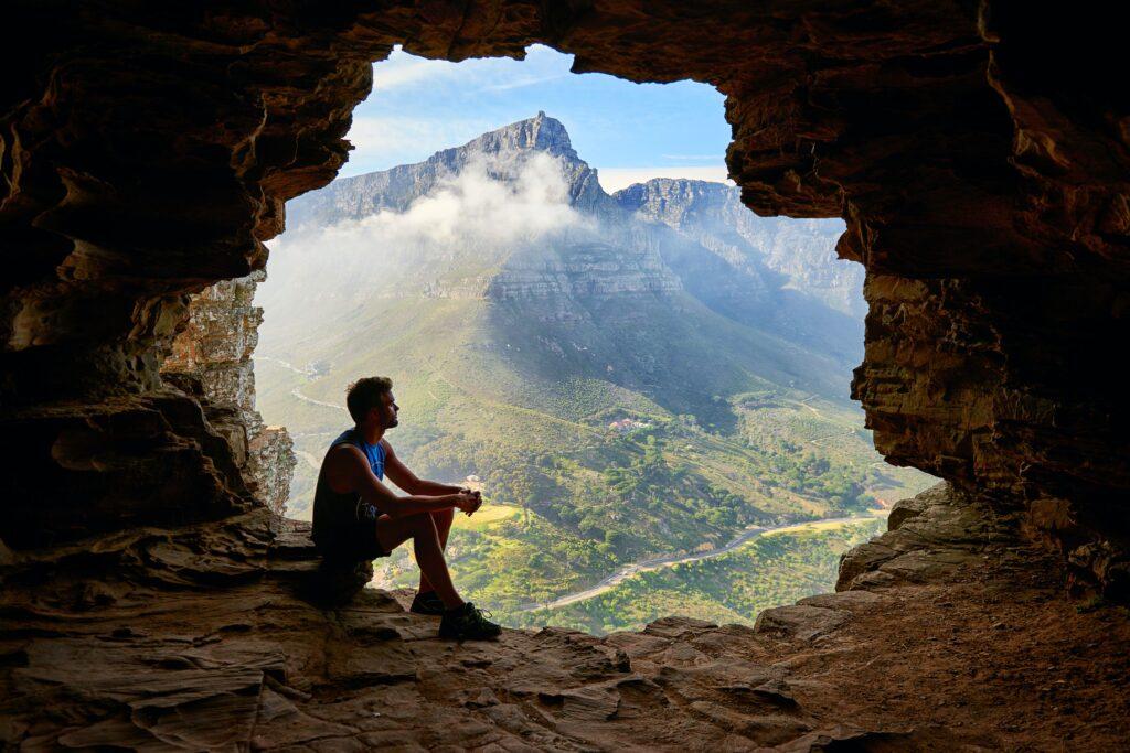 洞窟の中で座っている男性の画像
