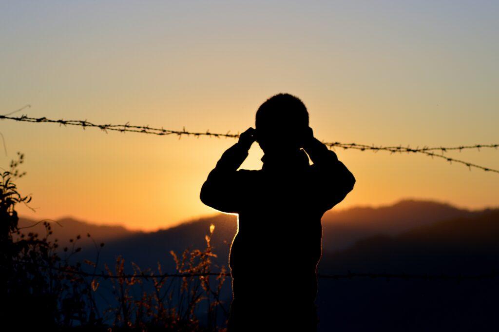 絶望的な人生から覚悟を決めたように夕焼けを眺めている男性のシルエットの画像