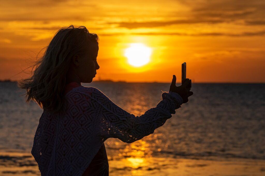 夕焼けに照らされてスマホを見ている女性の画像