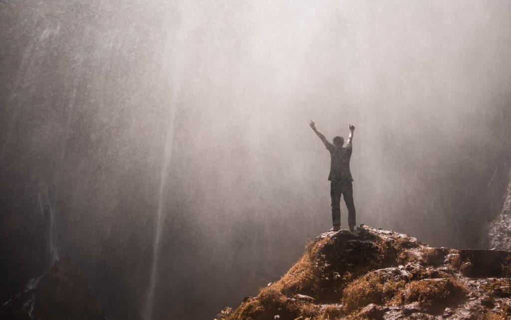 光差す岩の上に両手を上げて喜んでいる人のシルエットの画像
