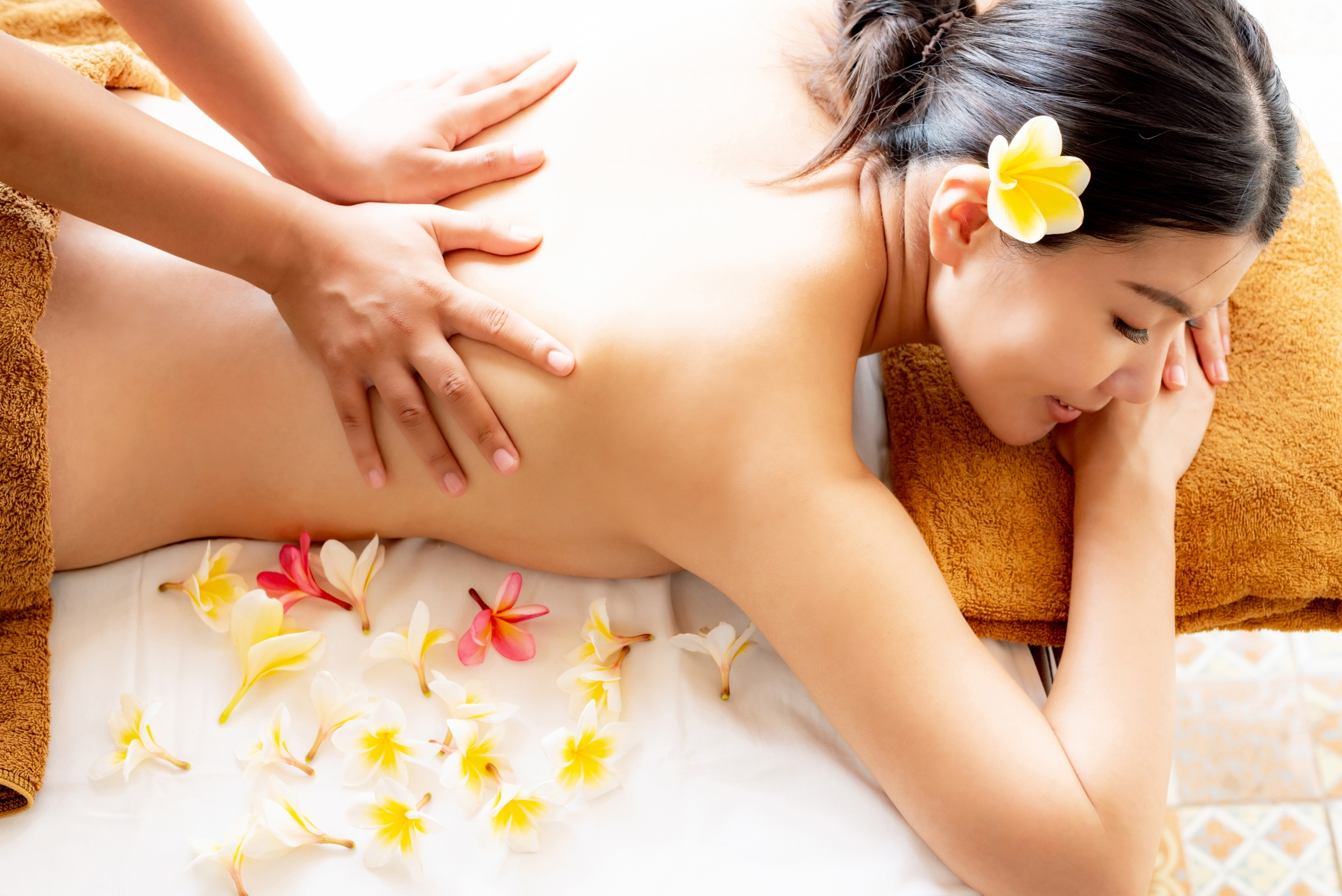 アロマセラピストが女性のお客さんの背中を施術している画像