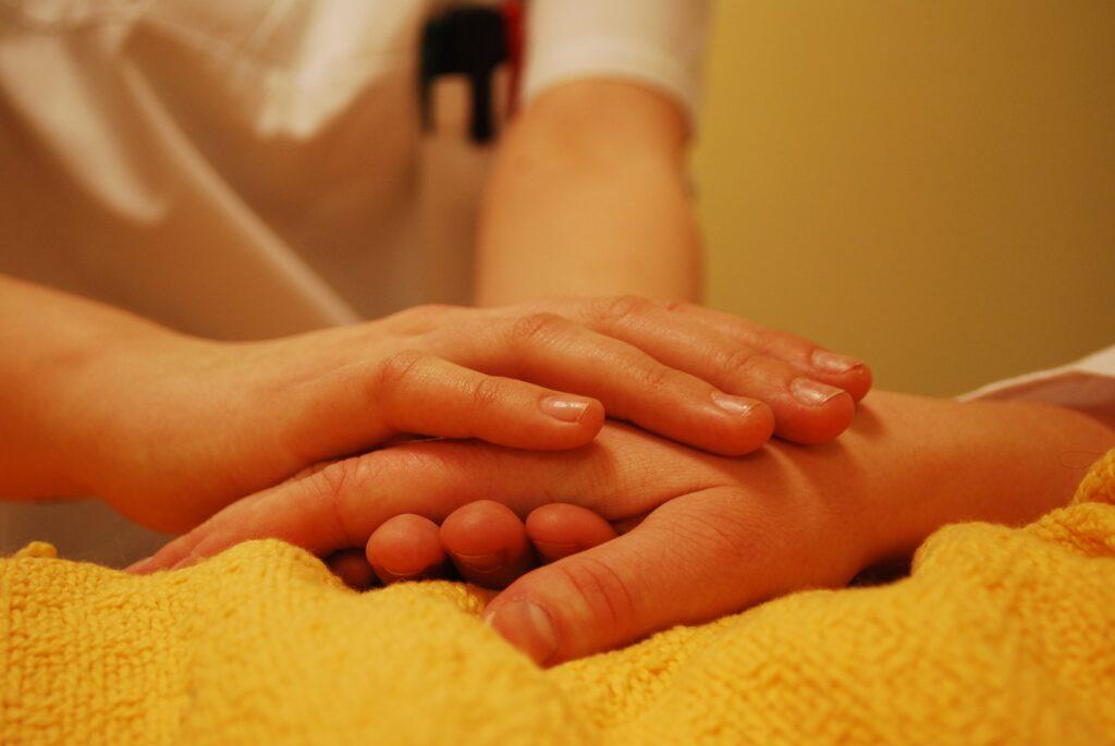 介護士が利用者の手を握っている画像
