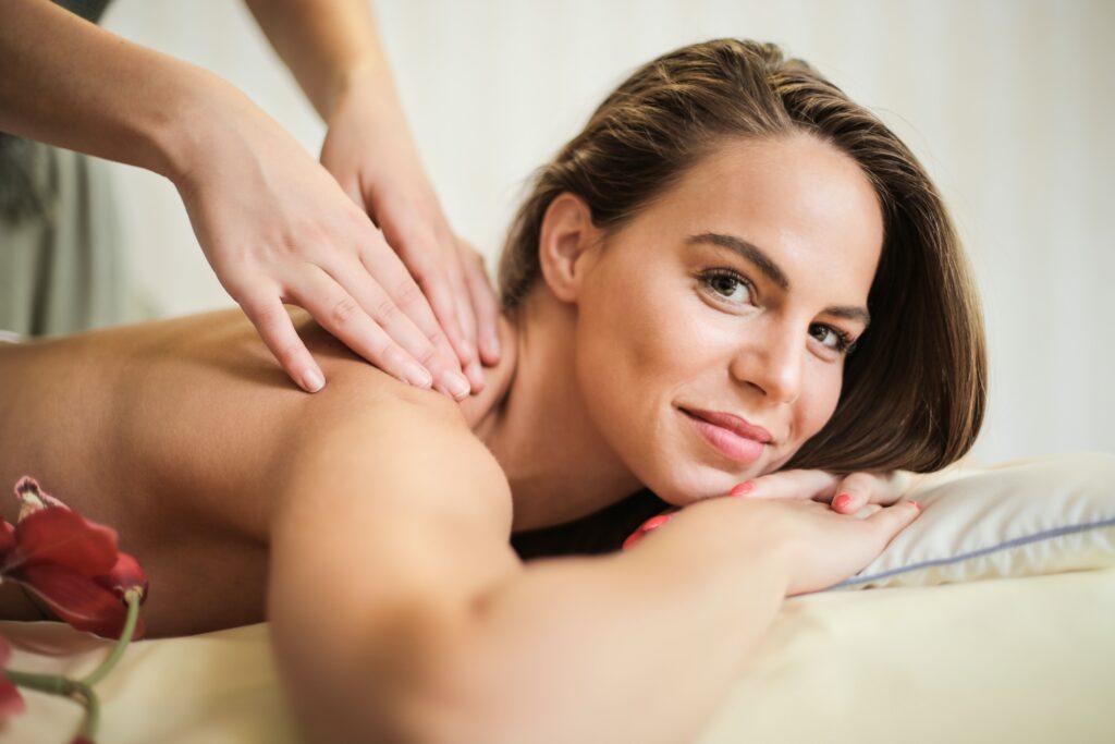 セラピストに肩を施術してもらっている女性の画像
