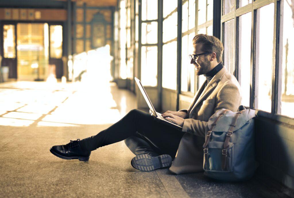 パソコンを開いて座っている男性の画像